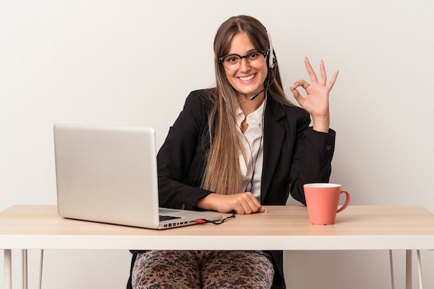 Young caucasian woman doing telecommuting isolated on white background cheerful and confident showing ok gesture.