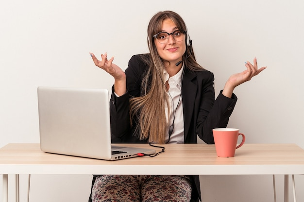 Young caucasian woman doing telecommuting isolated on white background doubting and shrugging shoulders in questioning gesture.