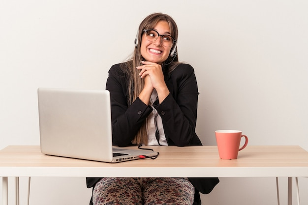 Young caucasian woman doing telecommuting isolated on white background keeps hands under chin, is looking happily aside.