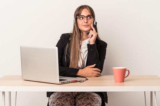 Young caucasian woman doing telecommuting isolated on white background looking sideways with doubtful and skeptical expression.