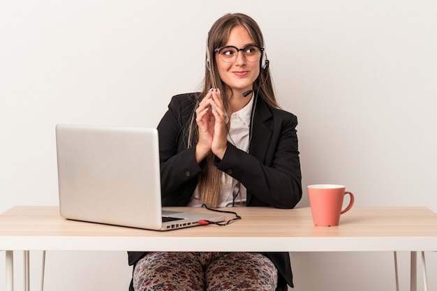 Young caucasian woman doing telecommuting isolated on white background making up plan in mind, setting up an idea.