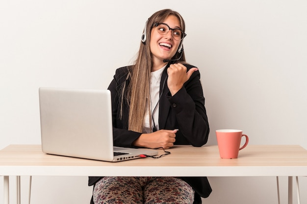 Young caucasian woman doing telecommuting isolated on white background points with thumb finger away, laughing and carefree.