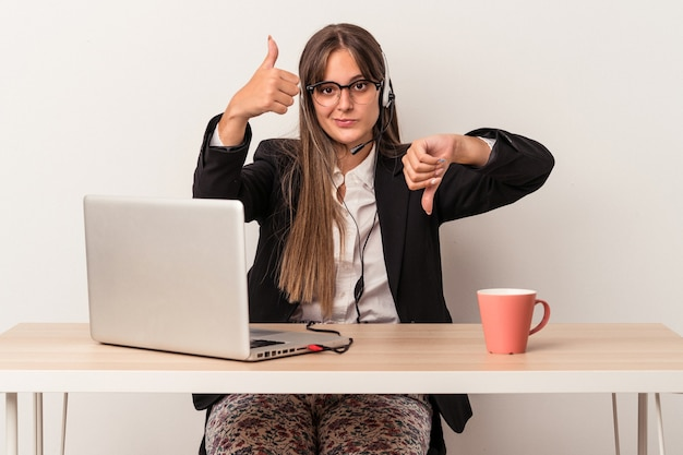 Young caucasian woman doing telecommuting isolated on white background showing thumbs up and thumbs down, difficult choose concept