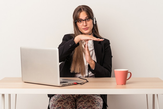 Young caucasian woman doing telecommuting isolated on white background showing a timeout gesture.