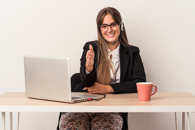 Young caucasian woman doing telecommuting isolated on white background stretching hand at camera in greeting gesture.