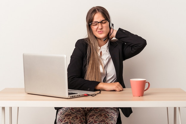 Young caucasian woman doing telecommuting isolated on white background suffering neck pain due to sedentary lifestyle.