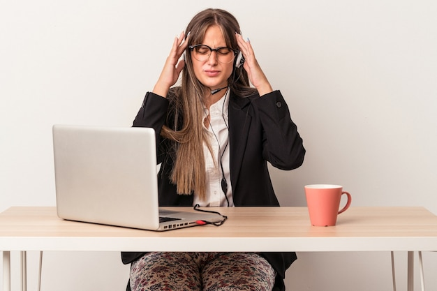 Young caucasian woman doing telecommuting isolated on white background touching temples and having headache.