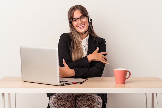 Young caucasian woman doing telecommuting isolated on white background who feels confident, crossing arms with determination.