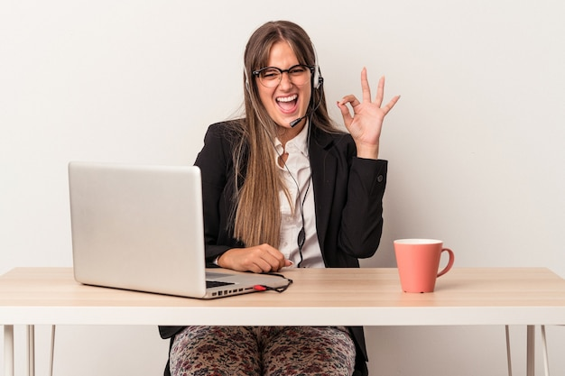 Young caucasian woman doing telecommuting isolated on white background winks an eye and holds an okay gesture with hand.