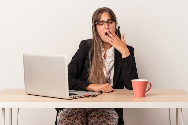 Young caucasian woman doing telecommuting isolated on white background yawning showing a tired gesture covering mouth with hand.