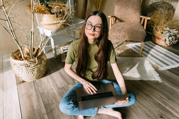 若い白人女性は、晴れた日に居心地の良い家の床に座って、ラップトップコンピューターで作業しながら夢を見ました