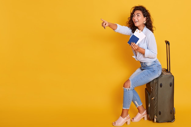 Young caucasian woman, dressed casual clothing, holding passport with flying tickets while sitting on suitcase