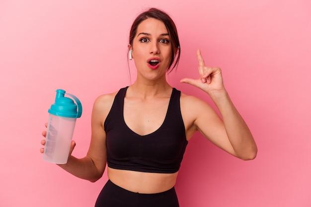 アイデア、インスピレーションの概念を持つピンクの背景に分離されたプロテインシェイクを飲む若い白人女性。