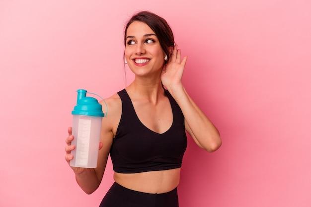 ゴシップを聴こうとしているピンクの背景に分離されたプロテインシェイクを飲む若い白人女性。