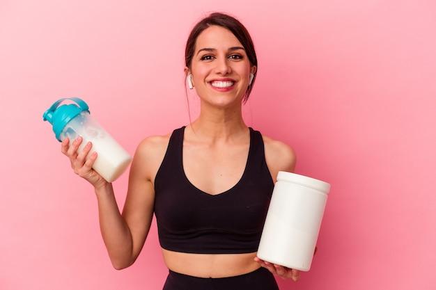ピンクの背景に分離されたプロテインシェイクを飲む若い白人女性