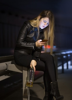술을 마시고 밤에 거리에 메시지를 입력하는 젊은 백인 여자
