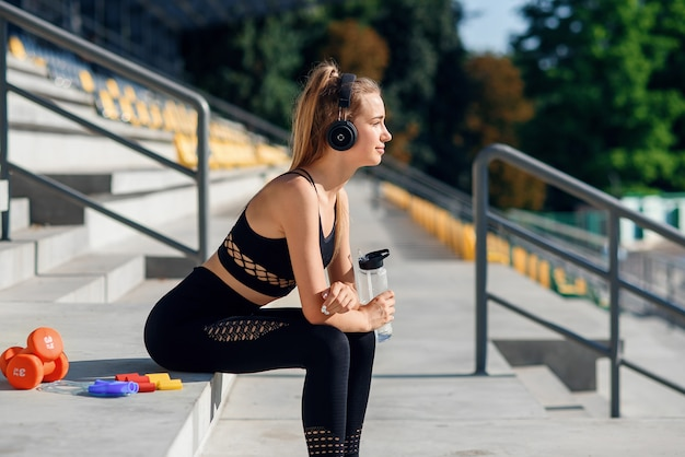 Young caucasian woman drinks water and listen to music after training.