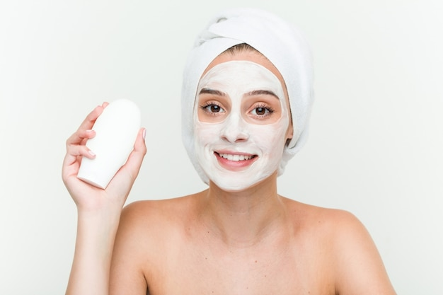 Young caucasian woman enjoying of a facial mask treatment with a moisturizer bottle