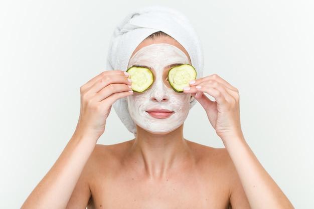 Young caucasian woman enjoying offacial mask treatment with cucumber