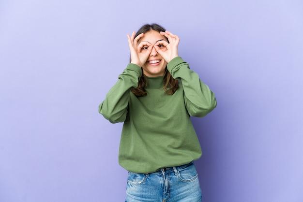 Молодая кавказская женщина взволнована, держа одобренный жест на глазах.