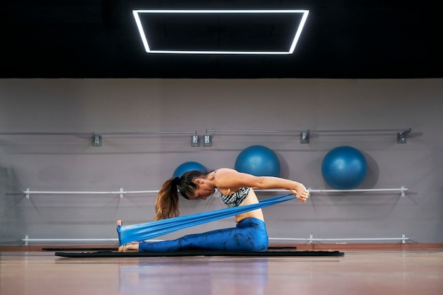 Young caucasian woman exercising pilates fitness sturdy elastic band exercises in a modern gym.