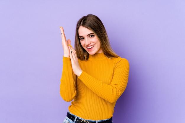 Молодая кавказская женщина чувствует себя энергичной и комфортной, уверенно потирая руки.