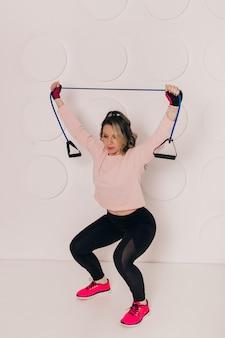 Молодая кавказская женщина фитнес-инструктор тренируется перед белой стеной с резиновой лентой сопротивления