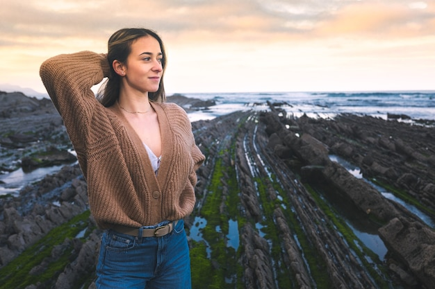 Young caucasian woman at the flysch geopark at the basque country.
