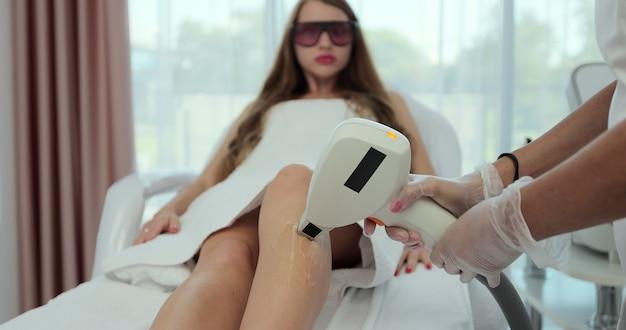 Молодая кавказская женщина, получающая лазерную эпиляцию в салоне красоты. нежелательные волосы и концепция лазерной эпиляции.