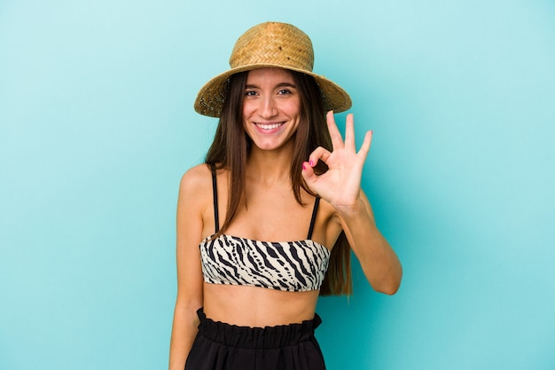 Young caucasian woman going to the beach wearing bikini isolated on blue background cheerful and confident showing ok gesture.