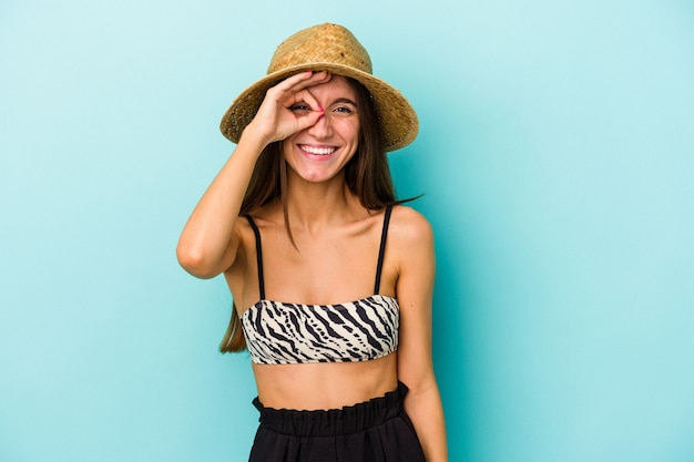 Young caucasian woman going to the beach wearing bikini isolated on blue background excited keeping ok gesture on eye.