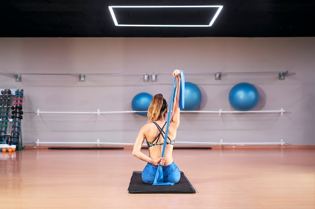 Young caucasian woman in a gym exercising pilates fitness sturdy elastic band exercises.
