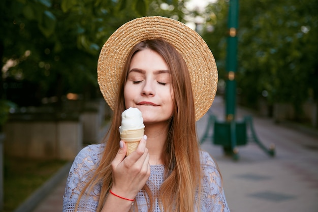 Young caucasian woman in hat enjoying ice cream outdoors in summer