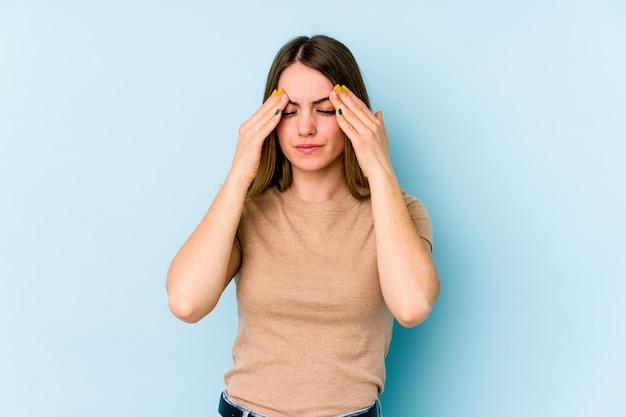 Молодая кавказская женщина, имеющая головную боль, касаясь передней части лица.