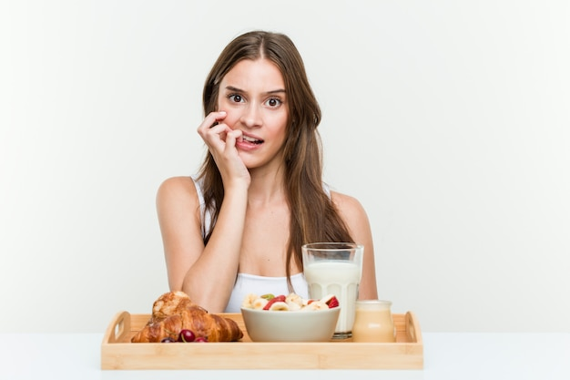 Young caucasian woman having breakfast biting fingernails, nervous and very anxious.