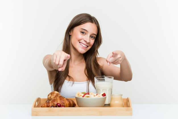 Young caucasian woman having breakfast cheerful smiles pointing to front.