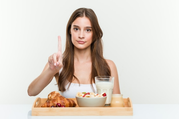 Young caucasian woman having breakfast showing number one with finger.