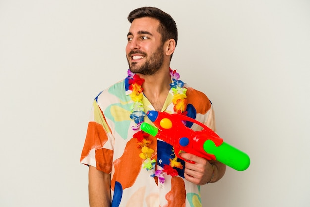 Young caucasian woman on a hawaiian party holding a water gun isolated on white wall looks aside smiling, cheerful and pleasant