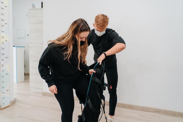 젊은 백인 여자가 그녀의 젊은 코치의 도움을 받아 운동을 위해 전기 자극 슈트를 입었습니다.