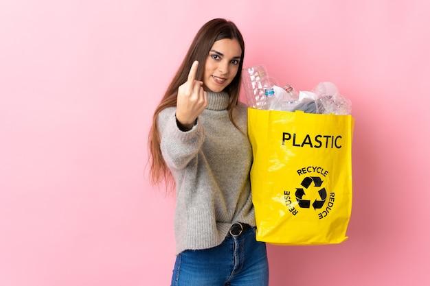 ペットボトルでいっぱいのバッグを持ってリサイクルする若い白人女性が来るジェスチャーをしているピンクで隔離