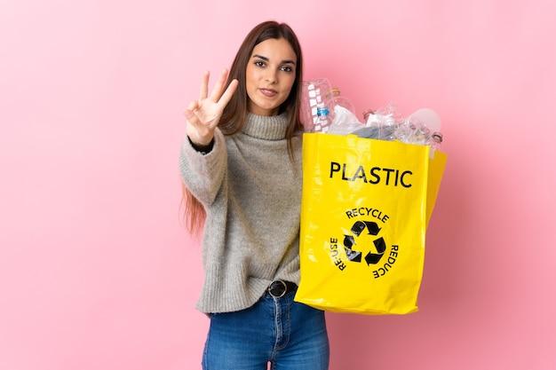 幸せなピンクの壁に隔離され、指で3を数えてリサイクルするためにペットボトルでいっぱいのバッグを保持している若い白人女性