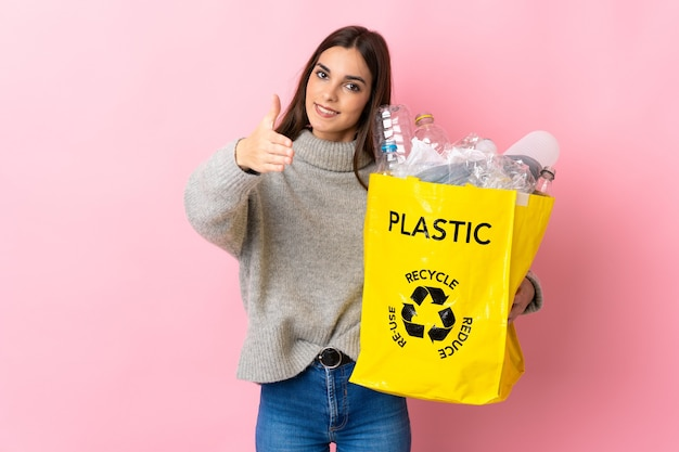 Молодая кавказская женщина, держащая мешок, полный пластиковых бутылок для переработки, изолирована на розовой стене, пожимая руку для заключения хорошей сделки
