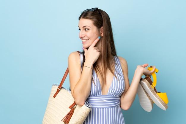 Молодая кавказская женщина, держащая пляжную сумку в летних сандалиях, изолирована на синем фоне и смотрит в сторону