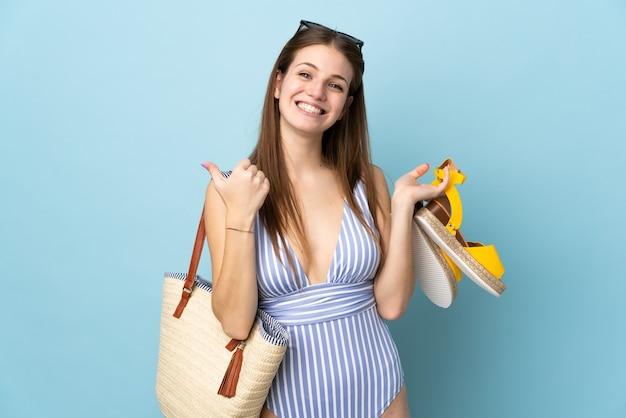 良いことが起こったので、青い背景に親指を立てて分離された夏のサンダル、ビーチ バッグを保持している若い白人女性