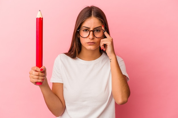 ピンクの背景に分離された大きな鉛筆を持っている若い白人女性は、指で寺院を指して、考えて、タスクに焦点を当てた。