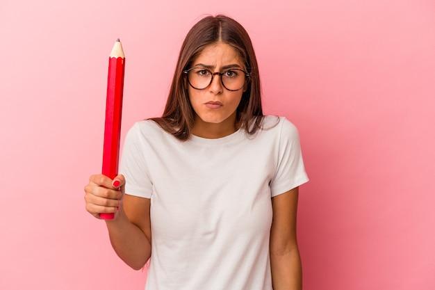 ピンクの背景に分離された大きな鉛筆を持っている若い白人女性は肩をすくめると混乱した目を開いています。