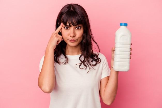 Молодая кавказская женщина держит бутылку молока, изолированную на розовом фоне, указывая висок пальцем, думая, сосредоточившись на задаче.