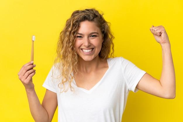 強いジェスチャーをしている黄色の背景に分離されたブラッシング歯を保持している若い白人女性 Premium写真