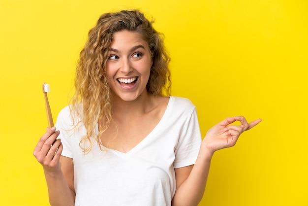 指を持ち上げながら解決策を実現しようと黄色の背景に分離されたブラッシング歯を保持している若い白人女性