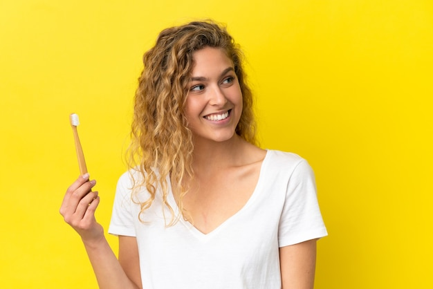 横を見て笑っている黄色の背景に分離されたブラッシング歯を保持している若い白人女性 Premium写真